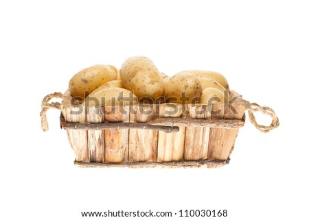 bunch of freshly harvested potatoes in a wooden basket on a white background - stock photo