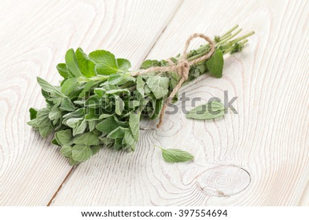Bunch of garden oregano herb on wooden table