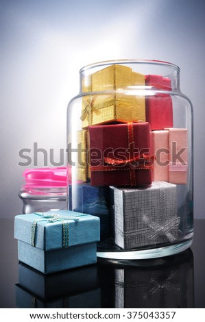 Bunch of gift boxes filling a glass flask