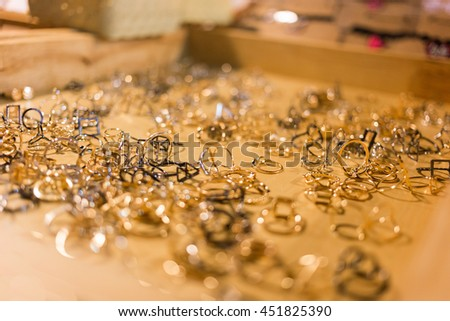 Bunch of gold jewelry against black background - stock photo