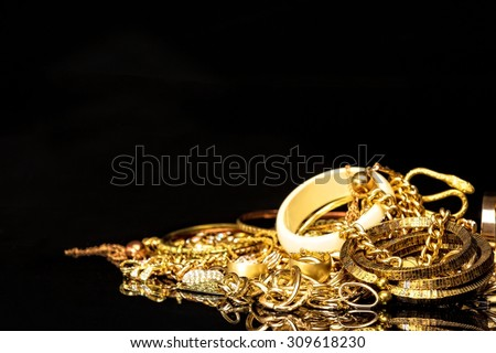 Bunch of gold jewelry against black background with copy space for text.