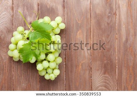 Bunch of grapes on wooden table background with copy space