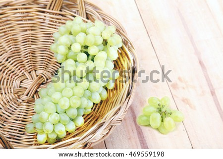 Bunch of grapes with green vine leaves in basket on wooden table .