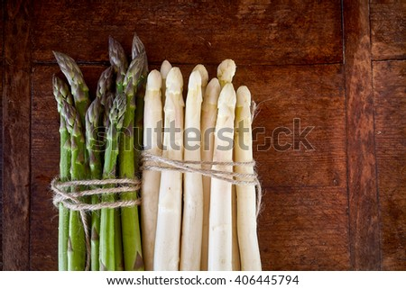 Bunch of Green and white asparagus on brown wooden background or board for new summer food concepts. - stock photo