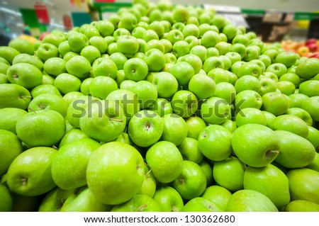 Bunch of green apples in supermarket. Wide angle shot - stock photo