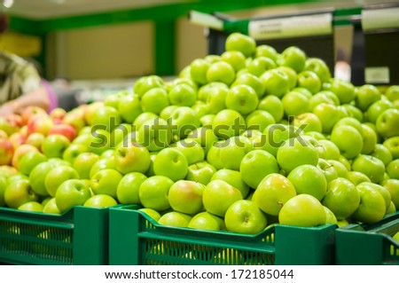 Bunch of green apples on boxes in supermarket