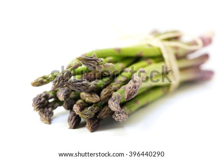 bunch of green asparagus isolated with a small shadow on a white background, closeup with selected focus, very narrow depth of field - stock photo