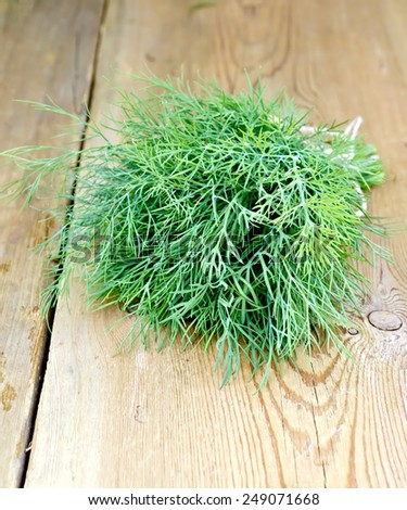 Bunch of green dill, tied with twine on a wooden boards background