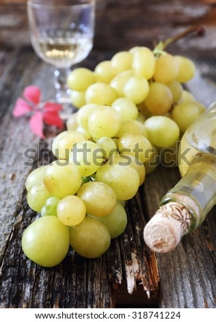 Bunch of green grapes and a bottle of white wine. Focus selective - stock photo