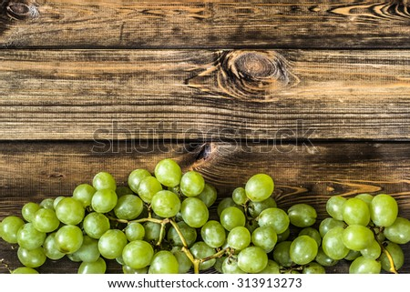 Bunch of green grapes, fruits of autumn, a symbol of abundance on rustic wood background with copy space, top view, close-up.