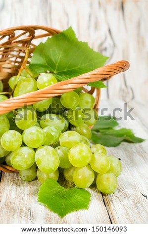 bunch of green grapes in a basket on a wooden background
