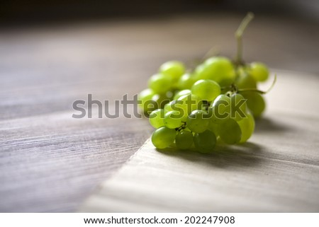 bunch of green grapes on wooden table - stock photo