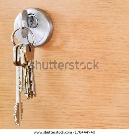 bunch of house keys in cylinder lock of wooden door - stock photo