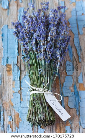 Bunch of lavender flowers with tag on an old wooden board. - stock photo