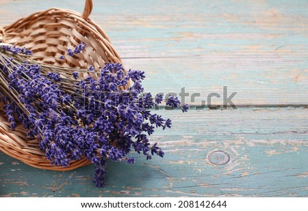 Bunch of lavender in wicker basket on a turquoise wooden table - stock photo