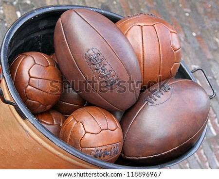 Bunch of leather sport balls in metal container