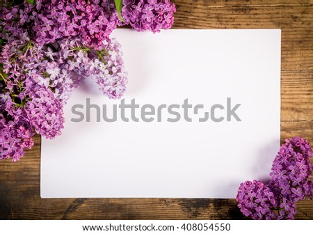 Bunch of lilac on brown wood old table with blank paper page, empty space for text - stock photo