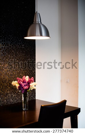 Bunch of lilac on the table in the local lighting by the wall, a modern kitchen interior closeup - stock photo