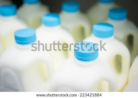 Bunch of milk bottles on fridge shelf in supermarket - stock photo