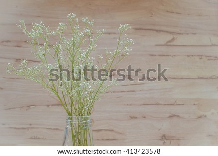 Bunch of Million star, Baby's-breath flowers, in glass vase is a small headed white Gypsophila flowers on wooden background with copy space. - stock photo
