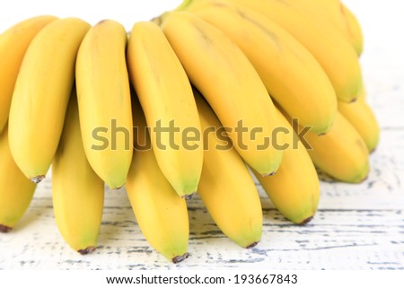 Bunch of mini bananas on color wooden background