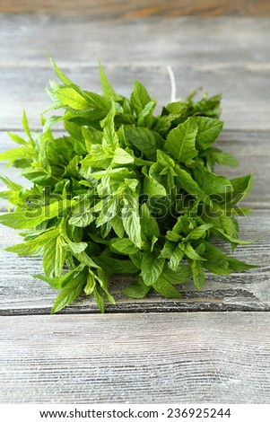Bunch of mint on the boards, wooden background - stock photo
