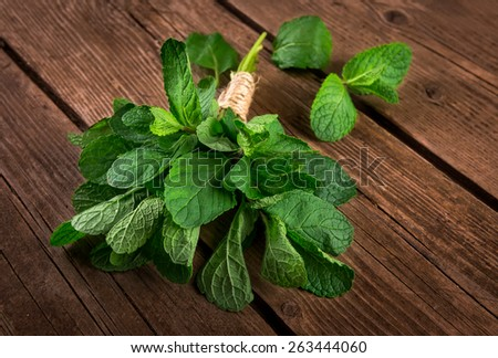 Bunch of mint on the wooden background - stock photo