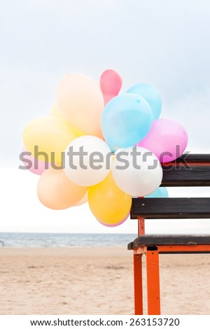 Bunch of multicolored air balloons attached to wooden bench on blue sky backgorund. Outdoors. - stock photo