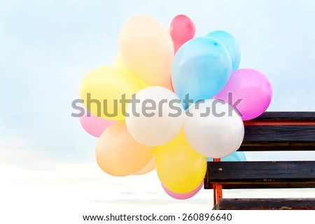 Bunch of multicolored air balloons attached to wooden bench on blue sky background. Outdoors. - stock photo