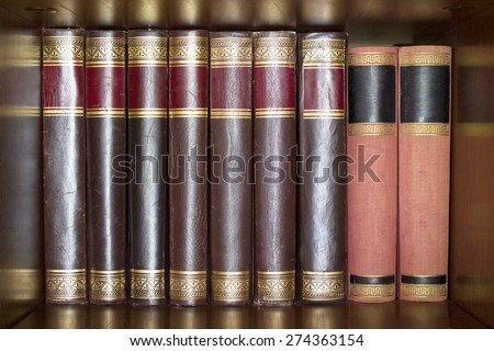 Bunch of old books on a wooden shelf lined up next to each other