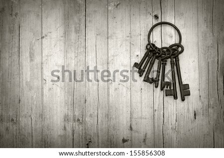 bunch of old keys on wooden background black and white - stock photo