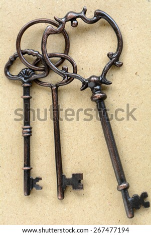 Bunch of old weathered keys on antique paper in vertical format - stock photo