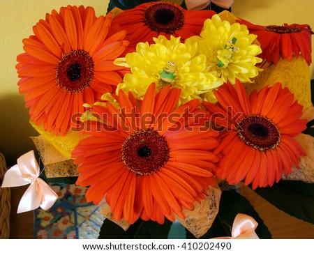 Bunch of orange and yellow color artificial flowers close up.