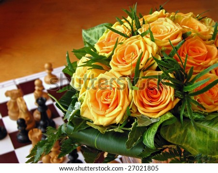 Bunch of orange roses with chess figures before wooden background - stock photo