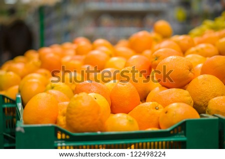 Bunch of oranges in boxes in supermarket - stock photo