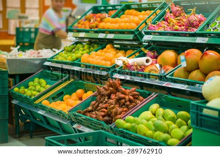 Bunch of oranges, lime, sala, pomelo, dragon fruits, mango in boxes in supermarket - stock photo