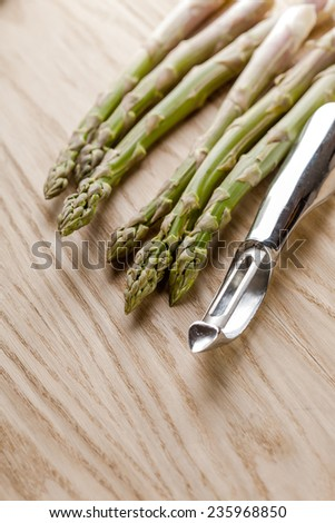 Bunch of organic asparagus and metal peeler on a table - stock photo
