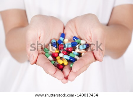 Bunch of pills in female hands. Selective focus on the front pills in hands - stock photo