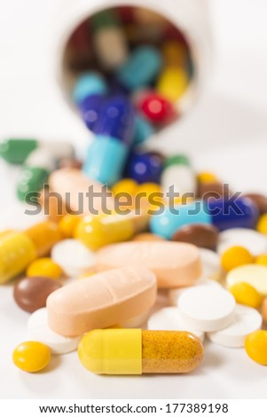 Bunch of pills on white background.Selective focus on the front yellow pill - stock photo