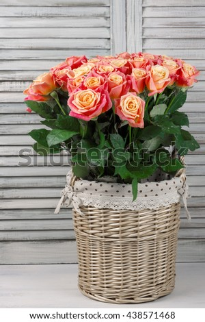 Bunch of pink rose flowers in wicker basket against shabby wooden shutters.