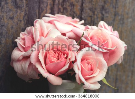 Bunch of pink roses against a wooden wall in a vintage style - stock photo