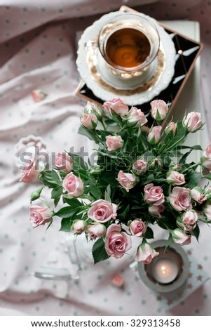 Bunch of pink roses set with a cup of tea and candles. Natural light photo. Shallow focus on the roses. Toned photo. - stock photo