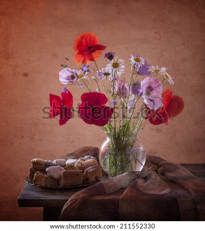 Bunch of poppies in vase on a wooden table