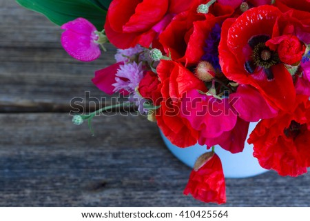 Bunch of Poppy, sweet pea and corn flowers  close up  on wooden background - stock photo