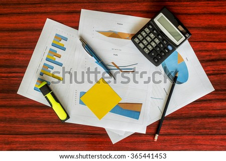 Bunch of printed charts and graphs with calculator, paper clips and pen on them