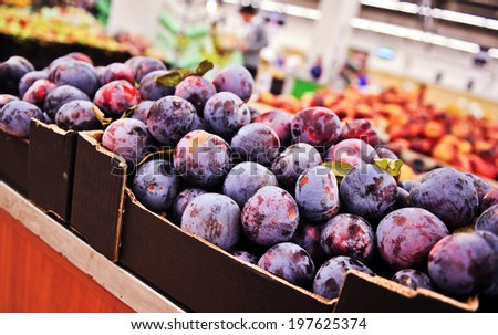 Bunch of purple plums in supermarket. Wide angle shot - stock photo