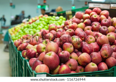Bunch of red and green  apples on boxes in supermarket - stock photo