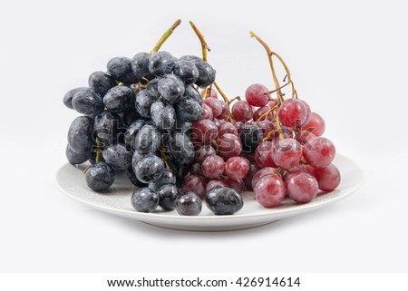 Bunch of red grapes , Bunch of Black grapes. Isolated on white background. on the white dish - stock photo