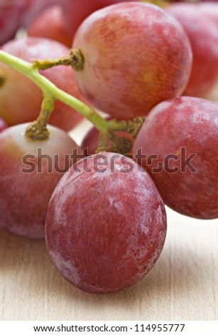 Bunch of red grapes on a wooden background - very shallow depth of field