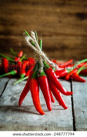 bunch of red hot chili peppers on a wooden rustic background - stock photo